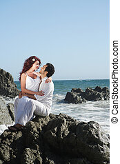 Young couple at the beach sitting on rocks