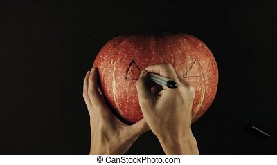 Male hands draws scary face jack o lantern on a pumpkin...