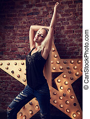 Happy blond young slim woman dancing in blue ripped jeans on yellow star and brick wall background. Toned portrait