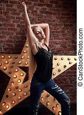 Happy blond young slim woman dancing in blue ripped jeans on yellow star and brick wall background