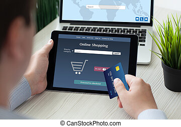 man holding tablet computer online shopping credit card near notebook