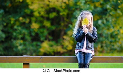 Portrait of adorable little girl with yellow leaf outdoors...