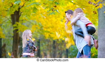 Happy family in autumn park outdoors. Happy kids ans dad throwing leaves around on an autumn day outdoors
