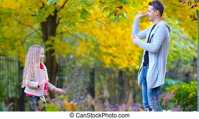 Adorable little girl and happy father enjoy fall day in autumn park outdoors. Autumn family vacation