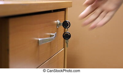 Desk drawer with a lock. The man opens the drawer locking...