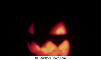 Halloween Jack o lantern with burning candle floats in dark space of alley