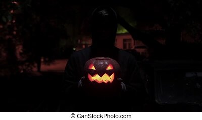 Black silhouette figure carries jack o lantern carved...