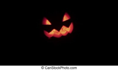 Halloween Jack o lantern with burning candle floats in dark...
