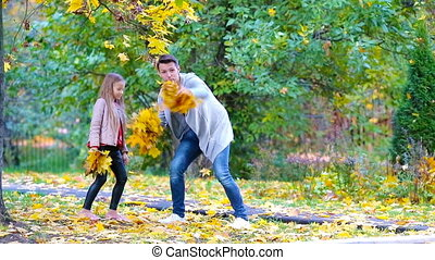 Adorable little girls and happy father with mother enjoy fall day in autumn park outdoors. Autumn family vacation