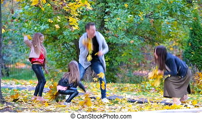 Young family of four throwing leaves around on an autumn day...