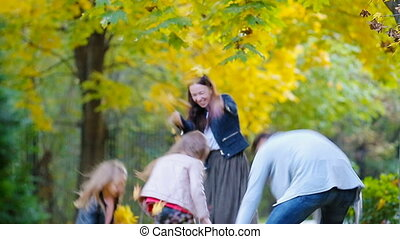 Young family have fun throwing leaves around on an autumn day outdoors