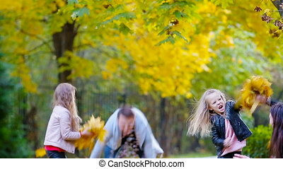 Young family have fun throwing leaves around on an autumn...