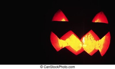 Young guy looks on burning candle inside of carved pumpkin jack o lantern face to face close up