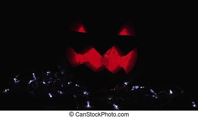 Halloween Jack o lantern with burning candle inside lay upon a white lights garland in dark