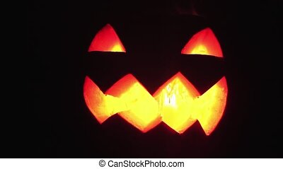 Candle burns inside jack o lantern on a halloween lot of...