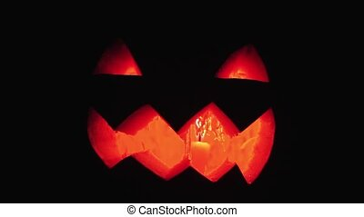 Candle burns inside jack o lantern on a halloween close up shot