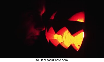 Young guy looks on burning candle inside of carved pumpkin...
