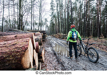Mountain biker riding cycling in wet autumn forest -...