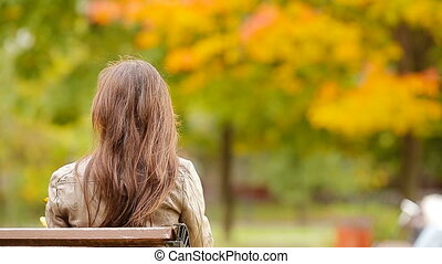 Beautiful woman enjoy warm day in autumn park under fall...