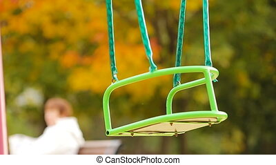 Closeup empty swing in autumn park outdoors - swing the...