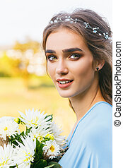 Beautiful young woman with long hair posing with bouquet