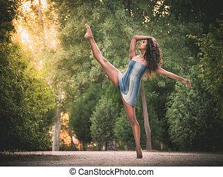Latin dancer with leg raised in road full of vegetation -...