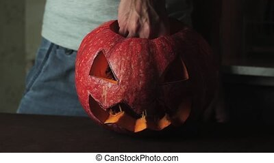 Male hands lights up candle inside jack o lantern then turns...