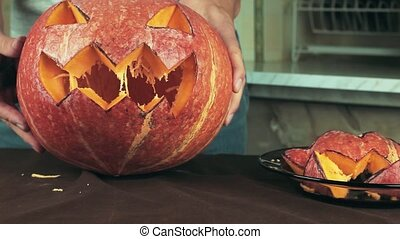 Freshly carved jack o lantern pumpkin in male hands on...