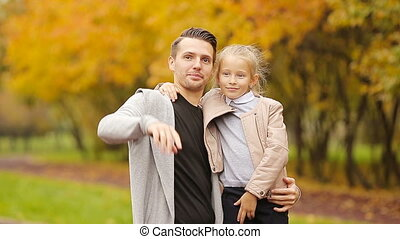 Portrait of little girl and happy father enjoy fall day in autumn park outdoors. Autumn family vacation