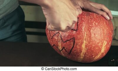 Young men carves jack o lantern out of pumpkin on a kitchen...