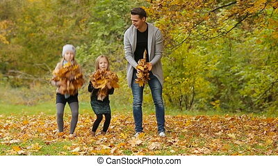 Young smiling family having fun and throwing leaves around on an autumn day outdoors