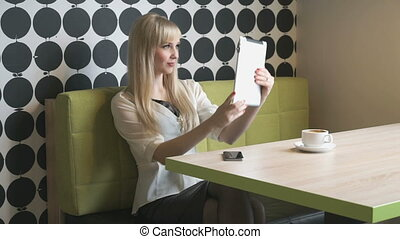 Girl makes selfie using a computer tablet