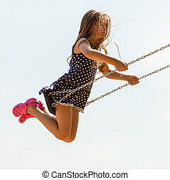 Girl swinging on swing-set. - Have fun and leisure concept....