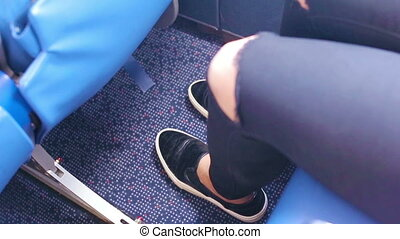 Young woman constrained on the plane. She stretches out her...