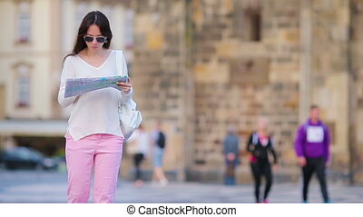 Happy young woman with a city map in Europe. Travel tourist...