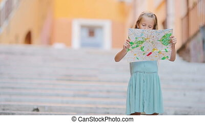 Adorable little girl with touristic map in roman streets in...