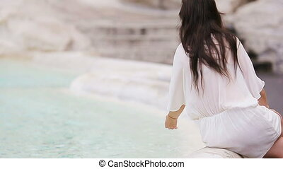 Beautiful woman near Trevi Fountain, Rome, Italy. Happy girl enjoy italian vacation holiday in Europe.