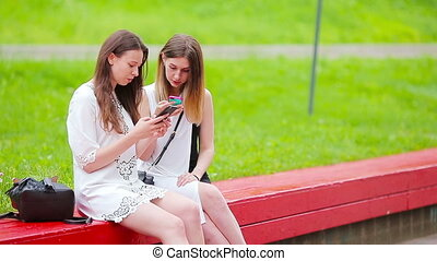 Two young girls using smart phones outdoors. Two women...