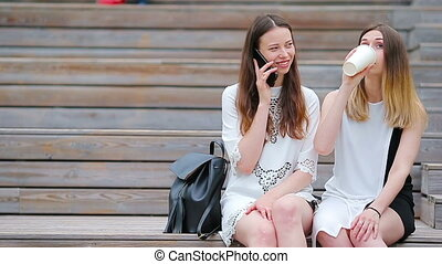 Two young girls using smart phone outdoors. Two women...