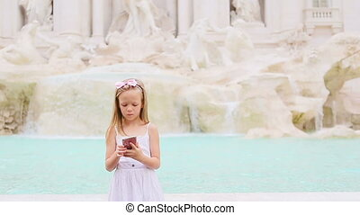 Adorable little girl with smart phone at warm day outdoors...