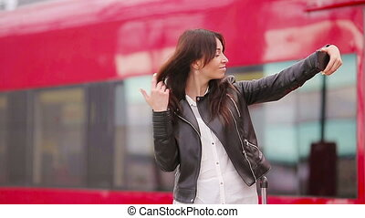 Young woman with luggage taking selfie at a train station....