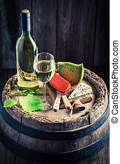 Chardonnay wine in glass with aromatic cheese on old barrel