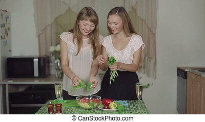 Women Cooking salad smiling on a Kitchen and Talking healthy food