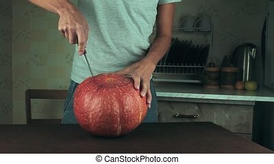 Young men carves jack o lantern out of pumpkin on a kitchen table using knife. Medium shot