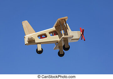 Wooden Plane flying with blue sky - Side view