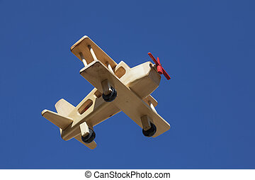 Wooden Plane flying with blue sky - Low angle shoot