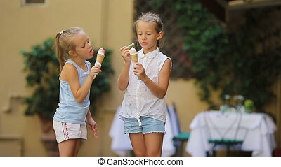 Adorable little girls eating ice-cream outdoors at summer....