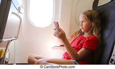 Adorable little girl traveling by an airplane sitting near window. Kid listening music sitting near aircraft window