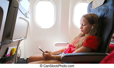 Adorable little girl traveling by an airplane sitting near window. Kid listening music and sending message sitting near aircraft window