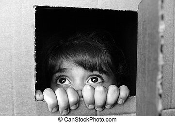 Face of afraid little girl peeking out from a cardboard box...